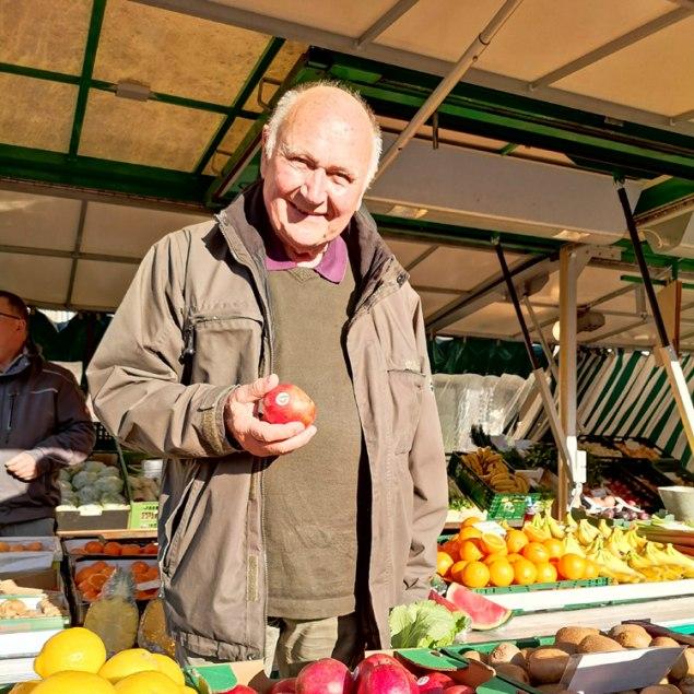 Hans Günther Kaufmann steht am Marktstand mit Apfel in der Hand, © Kulturamt der Stadt Miesbach